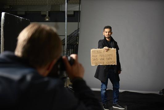 """Jeder hat das Recht auf Menschenrecht"""" sagt auch Ilkay Gündogan und hält beim Foto-Shooting Artikel 7 der Menschenrechte hoch"""