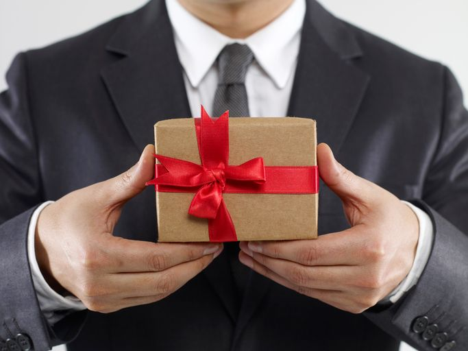 Kleine Geschenke erhalten die Freundschaft- und die Kundenbindung. Businessman holding gift box on white background