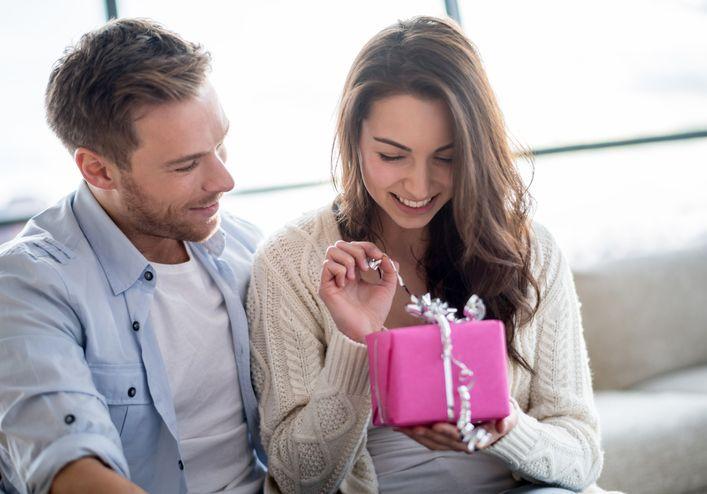 Schenken macht froh und glücklichWoman opening a present from her boyfriend
