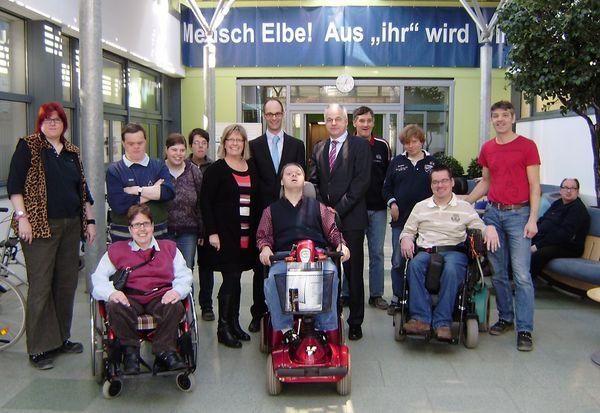 Beschäftigte der Elbe-Werkstätten und Gruppenleiter Jürgen Schaub (r.) freuen sich gemeinsam mit Andrea Matthiessen und Andre Schmeichel von der Firma PLUSS sowie Elbe-Geschäftsführer Rolf Tretow (Mitte, v.l.n.r.) über das gespendete Elektromobil