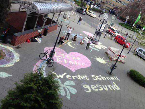 """Das prämierte Foto zeigt ein Kreidebild mit der Botschaft """"Liebe Kinder, werdet schnell gesund"""", das Friedensaktivisten in einer mit dem Klinikum unabgesprochenen Guerilla-Aktion als Genesungsgruß an die Kinder der Kinderchirurgie auf den Gehsteig gemalt hatten"""