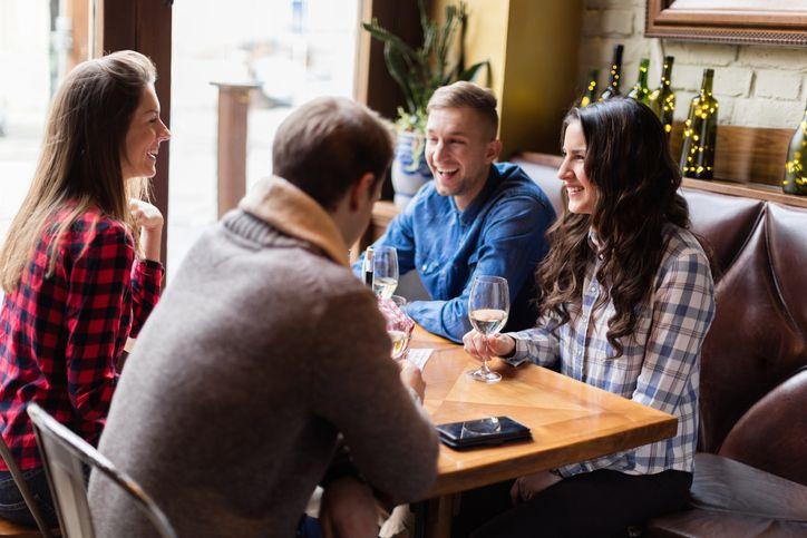 Friends socializing over white wine, smiling, sitting in restaurant
