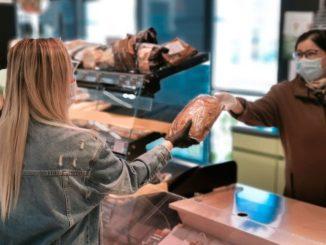 Frau mit Masken Schutz gegen den virus Covid 19 beim einkaufen im Lebensmittelladen