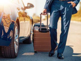 Mann mit Koffer am Auto